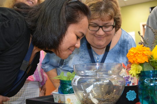 Isabel Quilang, RN,  and Dr. Jacqueline Bienenstock look at flowers and plants during Laura DePrado recent horticultural therapy program at Carrier Clinic in Montgomery.