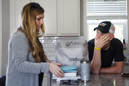 """Brice Udelhoven, 26, watches as his wife Margot packs a bag for bi-weekly trip to UI Hospitals from their home in Mingo on Thursday, Sept. 13, 2018. Since starting chemotherapy, Brice has lost 40 pounds. """"I have to keep some weight on him,"""" Margot said as she packed up a bag of snacks for their five-day stay at the hospital."""