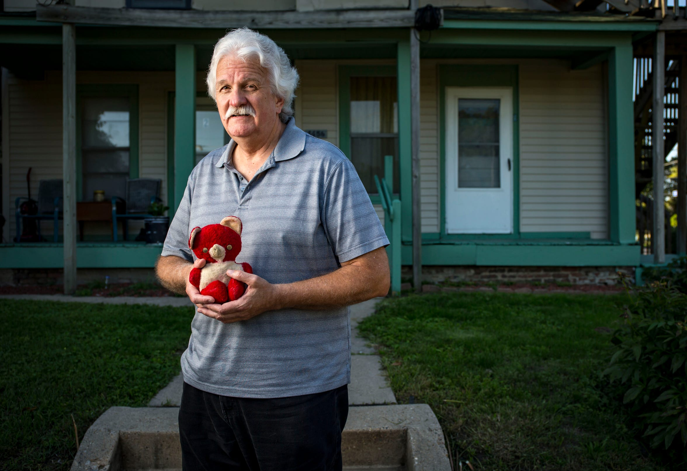 "Michael Banks holds a stuffed teddy bear Wednesday, Sept. 12, 2018, given to him by A.W ""Dub"" Barron at this location on Dean Ave. in Des Moines, Iowa. Michael Banks recalls breaking down outside his mother's house in Des Moines in Oct. of 1959 when he realized his father was leaving. ""He tried to console me by giving me a stuffed red-and-white bear from the back window of his car, where he had several,"" Banks said."