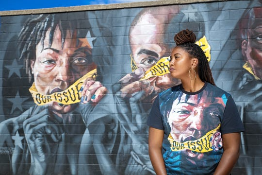 Desire Vincent Levy wears an Our Issue T-shirt while standing in front of the mural she and her husband, DeAndre Levy, had commissioned in Eastern Market to raise awareness about sexual assault and sexual violence.
