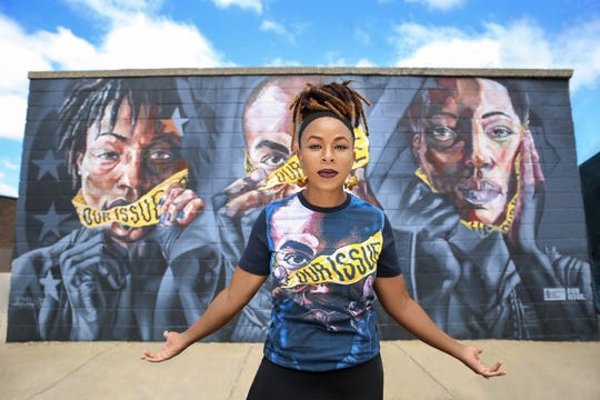 Artist Sydney G. James stands in front of mural she painted with AskewOne in Detroit's Eastern Market. She's wearing an Our Issue T-shirt being sold by Detroit Hustles Harder to raise money for organizations that support sexual assault survivors.