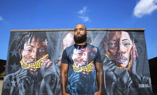 Former Detroit Lions linebacker DeAndre Levy wears an Our Issue T-shirt in front of the mural he and his wife, Desire Vincent Levy, had commissioned at Eastern Market to bring awareness to sexual assault and sexual violence.