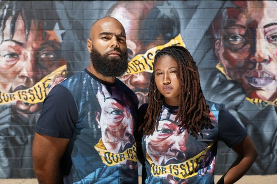 DeAndre and Desire Vincent Levy wear Our Issue T-shirts while standing in front of the mural they commissioned in Eastern Market to raise awareness about sexual assault and sexual violence.