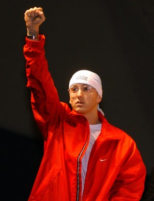 Rapper Eminem makes an entrance on the stage for the panel discussion during the Detroit Hip-Hop Summit at Cobo Arena in Detroit on  April 26, 2003.
