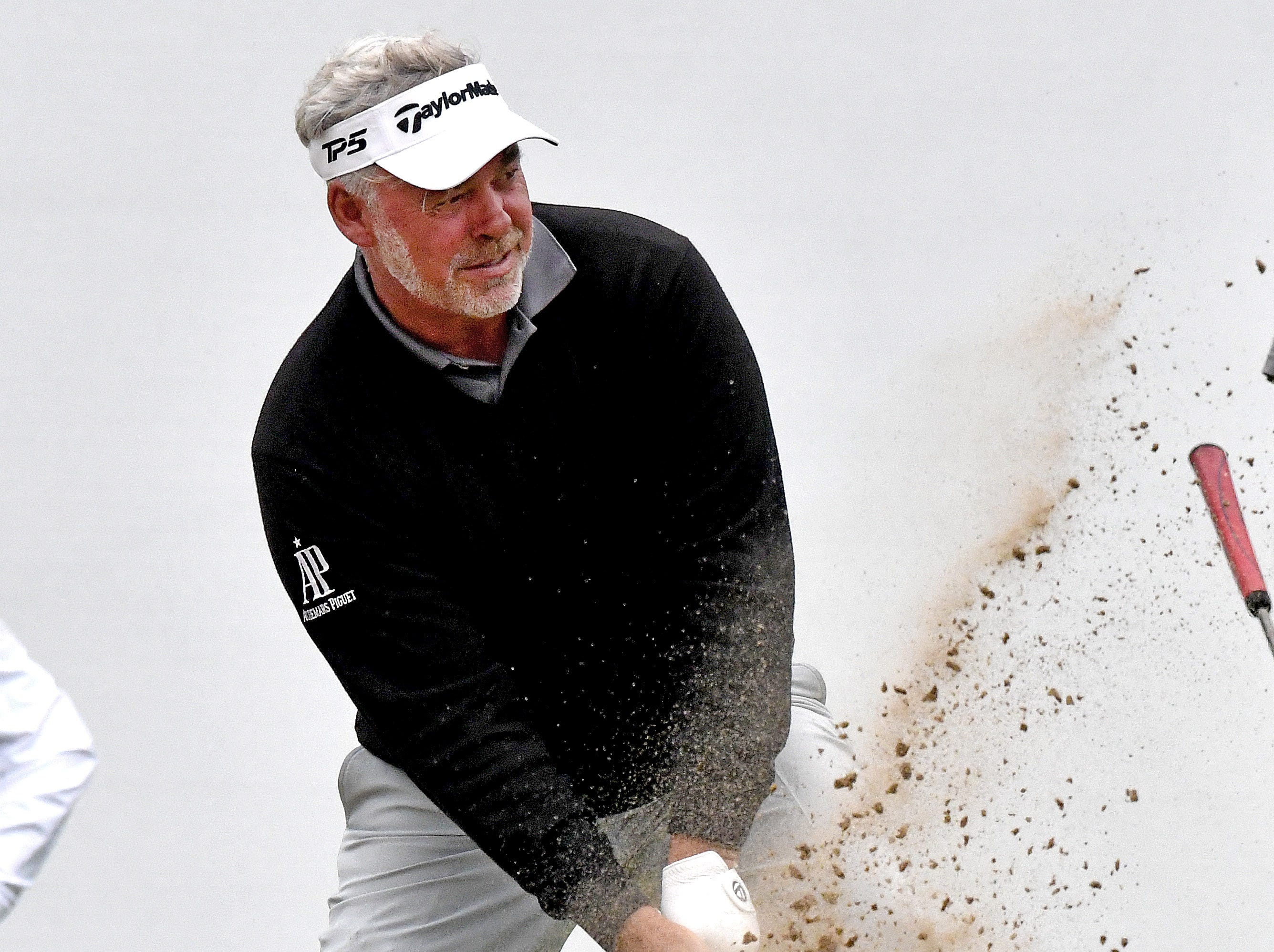 Darren Clarke catches the sand as he tries a shot while standing on the lip of the bunker next to the 18th green on Pro-Am day of the Ally Challenge at Warwick Hills Golf and Country Club in Grand Blanc.