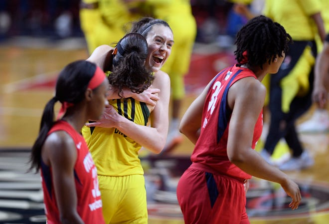 Seattle Storm forward Breanna Stewart, center, celebrates and hugs guard Sue Bird (10) after Game 3 of the WNBA finals as members of the Washington Mystics walk off the court on Wednesday.