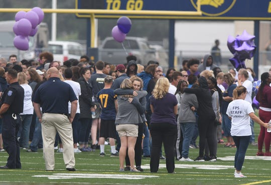 Parents, teachers, and students gatherand embrace at the Fitzgerald High School football field on Thursday in honor of Danyna Gibson, 16, who died after being stabbed by a classmate on Wednesday.