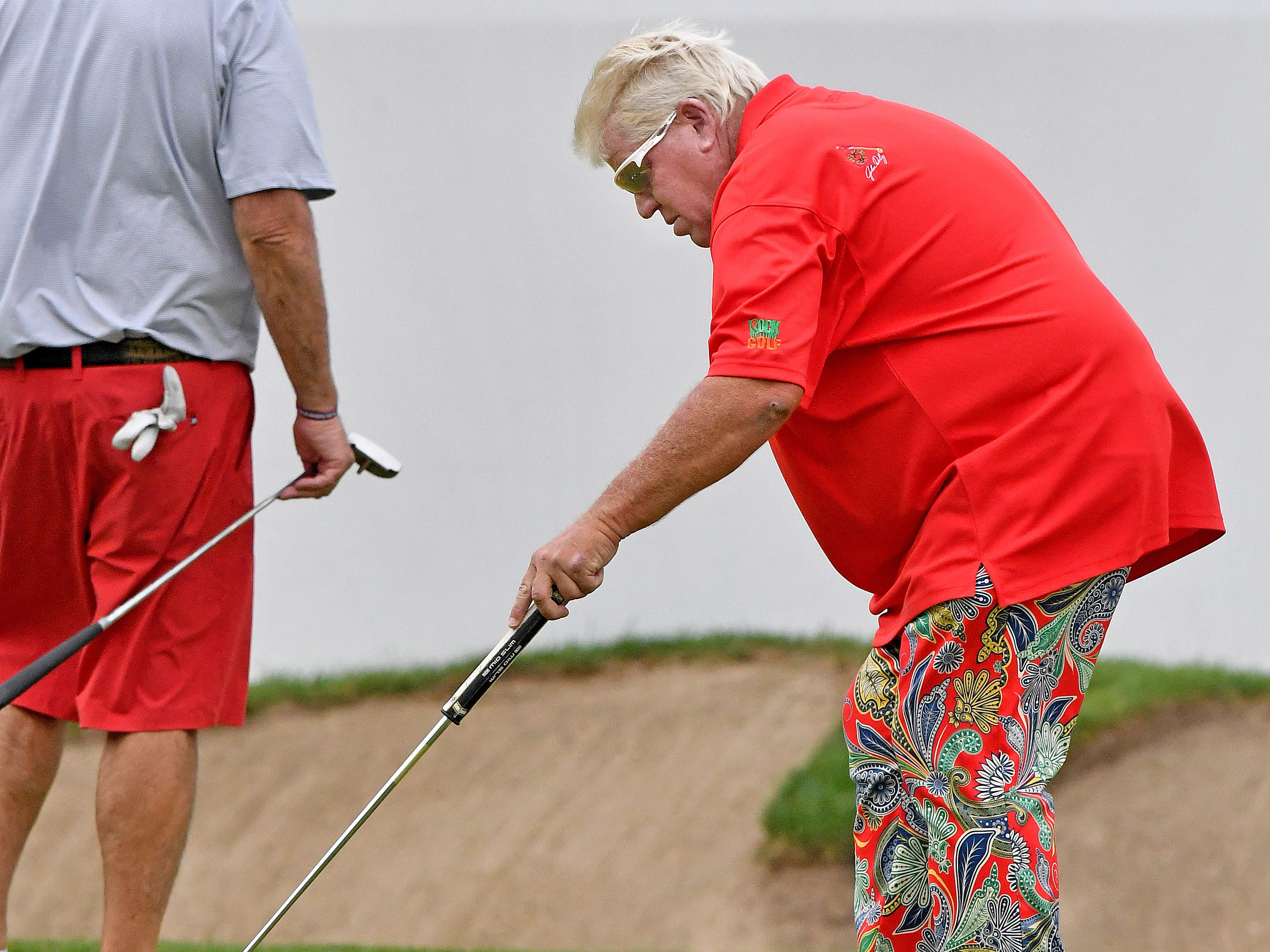 After missing his first putt on the 18th hole, John Daly scoops the ball toward him.
