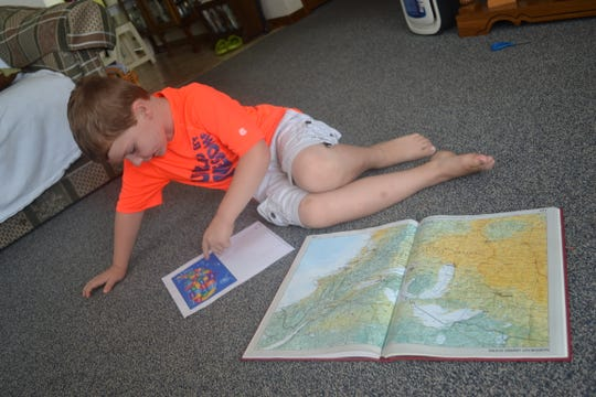 Atticus Ingram, 4, looks at one of his many maps, which are some of his favorite playthings, at the Fremont home he shares with his grandmother, Patricia Zilles.