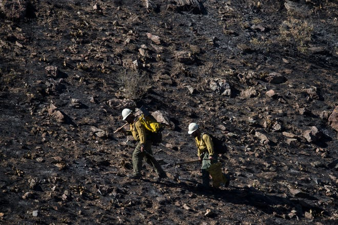 Firefighters hike up the charred hillside just North of Colorado Highway 14 opposite the Cache la Poudre River on Thursday, Sept. 13, 2018, in the Poudre Valley near Seaman Reservoir in Larimer County, Colo.