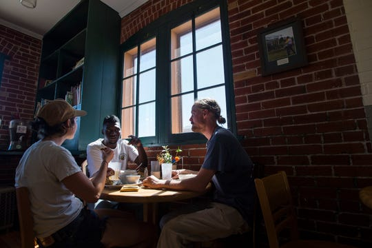 Local musicians, from left, Kaitlin Schramm, Phinehas and Andy Steiner eat lunch on Thursday, Sept. 13, 2018, at FoCo Cafe in Fort Collins, Colo.
