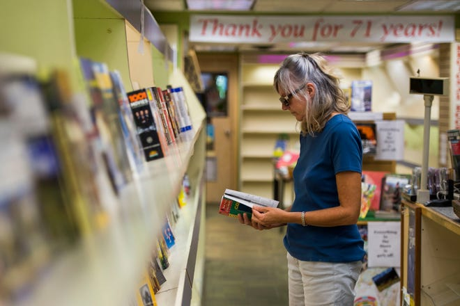 Longtime customer Jen Hultgren looks over what is left on the book racks on Thursday, Sept. 13, 2018, at Al's Newsstand in Old Town Fort Collins, Colo.