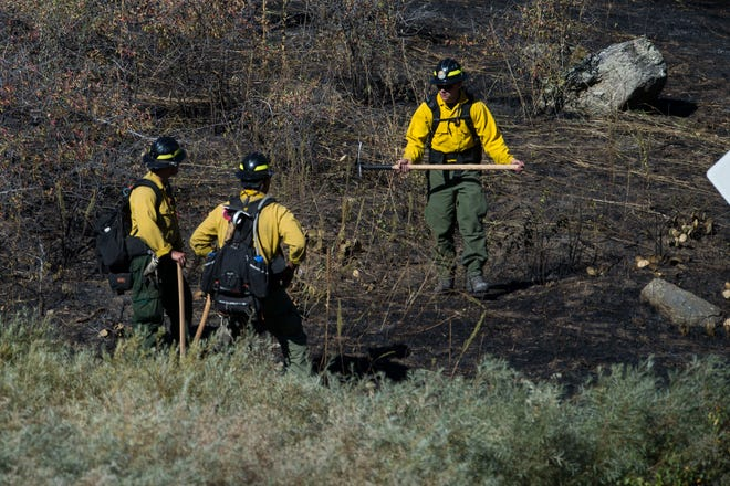 Firefighters mop up hotspots on the charred hillside just North of Colorado Highway 14 opposite the Cache la Poudre River on Thursday, Sept. 13, 2018, in the Poudre Valley near Seaman Reservoir in Larimer County, Colo.