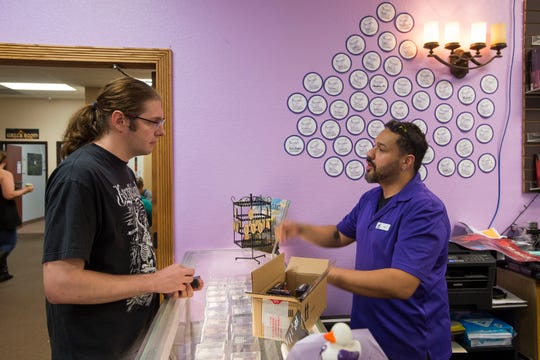 Comic book manager Nat Perez, right, talks to customer Matthew Denning about entry-level tactics of the competitive strategy and collector card game Magic: The Gathering on Wednesday, Sept. 12, 2018, at Gryphon Games and Comics in Fort Collins, Colo.