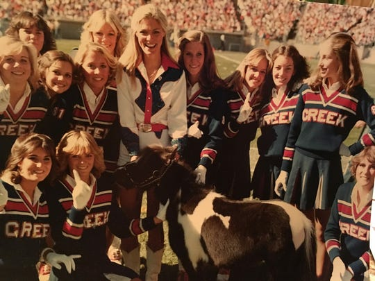T.D. posing with cheerleaders at Mile High Stadium.
