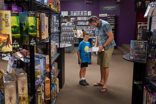 Peter Boyle and his son Connor, 9, check out the competitive legacy boardgame Charterstone while on Wednesday, Sept. 12, 2018, at Gryphon Games and Comics in Fort Collins, Colo.