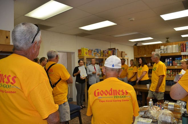 """Cape Coral Council member Jessica Cosen, middle background, reads a proclaim declaring Sept. 13 """"Goodness-To-Go Day"""" in front of Cape Coral Caring center volunteers."""
