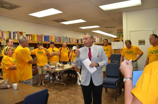 """Chris Spiro, middle, board member of the Cape Coral Caring Center, talks to volunteers about the """"Goodness To-Go Event,"""" which brought in thousands of pounds of foods and over $33,000."""