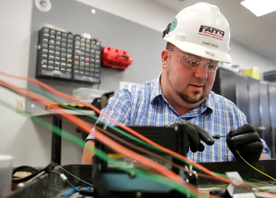 Charles Nelson, a specialty systems apprentice level three, works on fusion splicing fiberoptic cables in his electronic systems apprenticeship program course on Sept. 11 in Appleton.