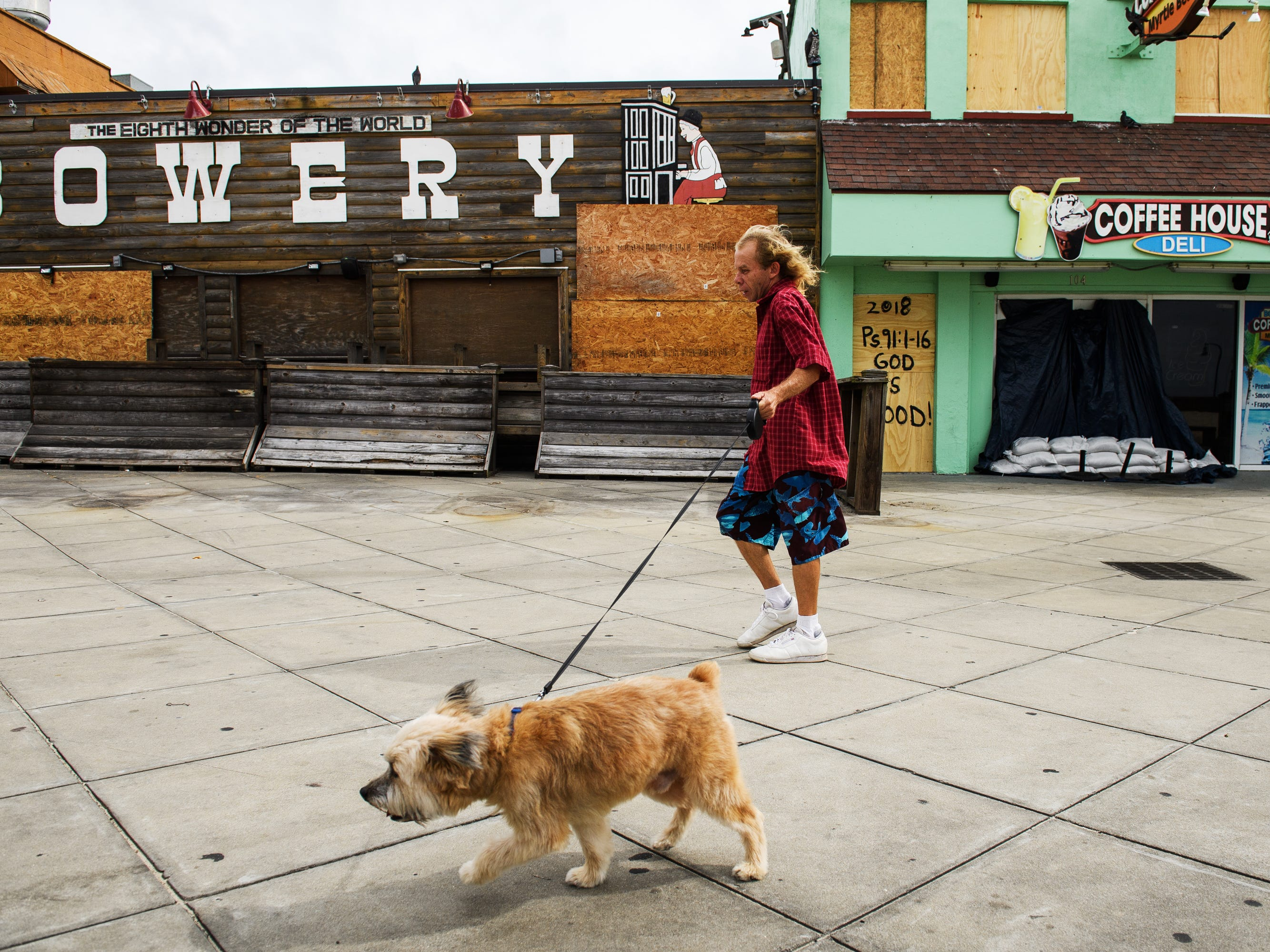 James Blackman walks his dog Marley in front of boarded up businesses at the Myrtle Beach Boardwalk and Promenade on Thursday, Sept. 13, 2018.