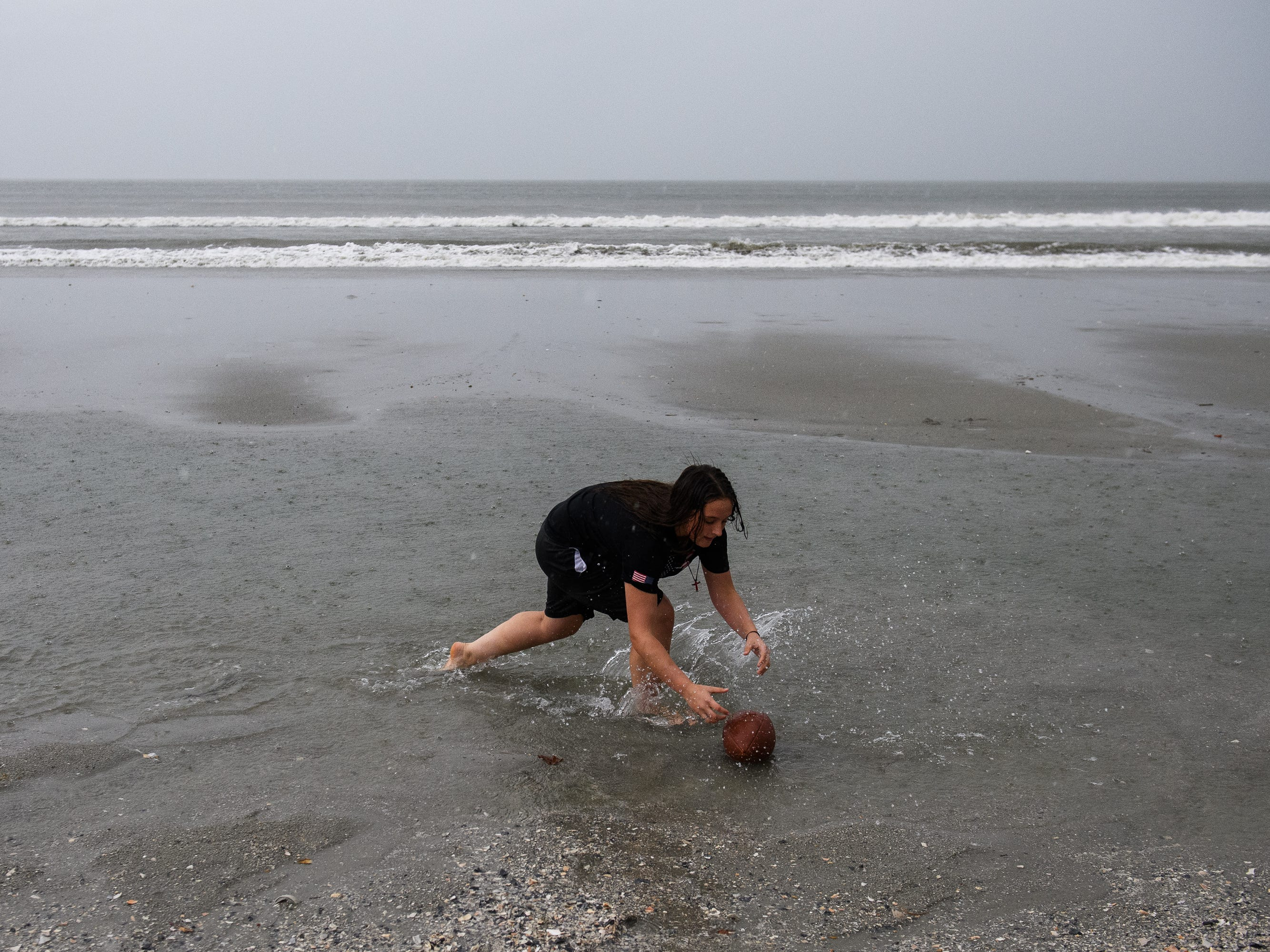 Haleigh Washington, 13, plays catch at Cherry Grove Beach in North Myrtle Beach as the first rain from a stray outer band of Hurricane Florence hits the area on Thursday, Sept. 13, 2018.