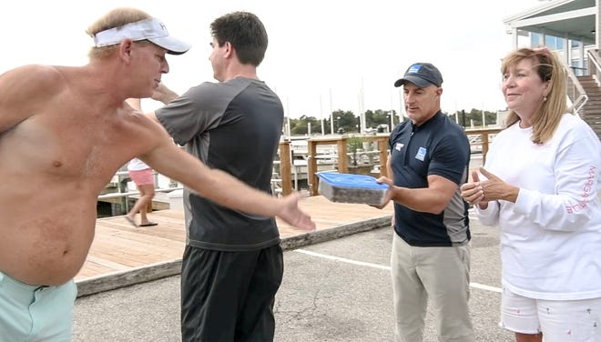 Will Clardy, left, a resident of Wilmington for 51 years, presents Jim Cantore, The Weather Channel, middle, with freshly made boiled peanuts near Kathy Gresham of Wilmington, who works at New Hanover Regional Medical Center, between a live interview, before Hurricane Florence in Wilmington, North Carolina on Thursday, September 13, 2018. (Ken Ruinard / Greenville News / Gannett USA Today Network / 2018 )