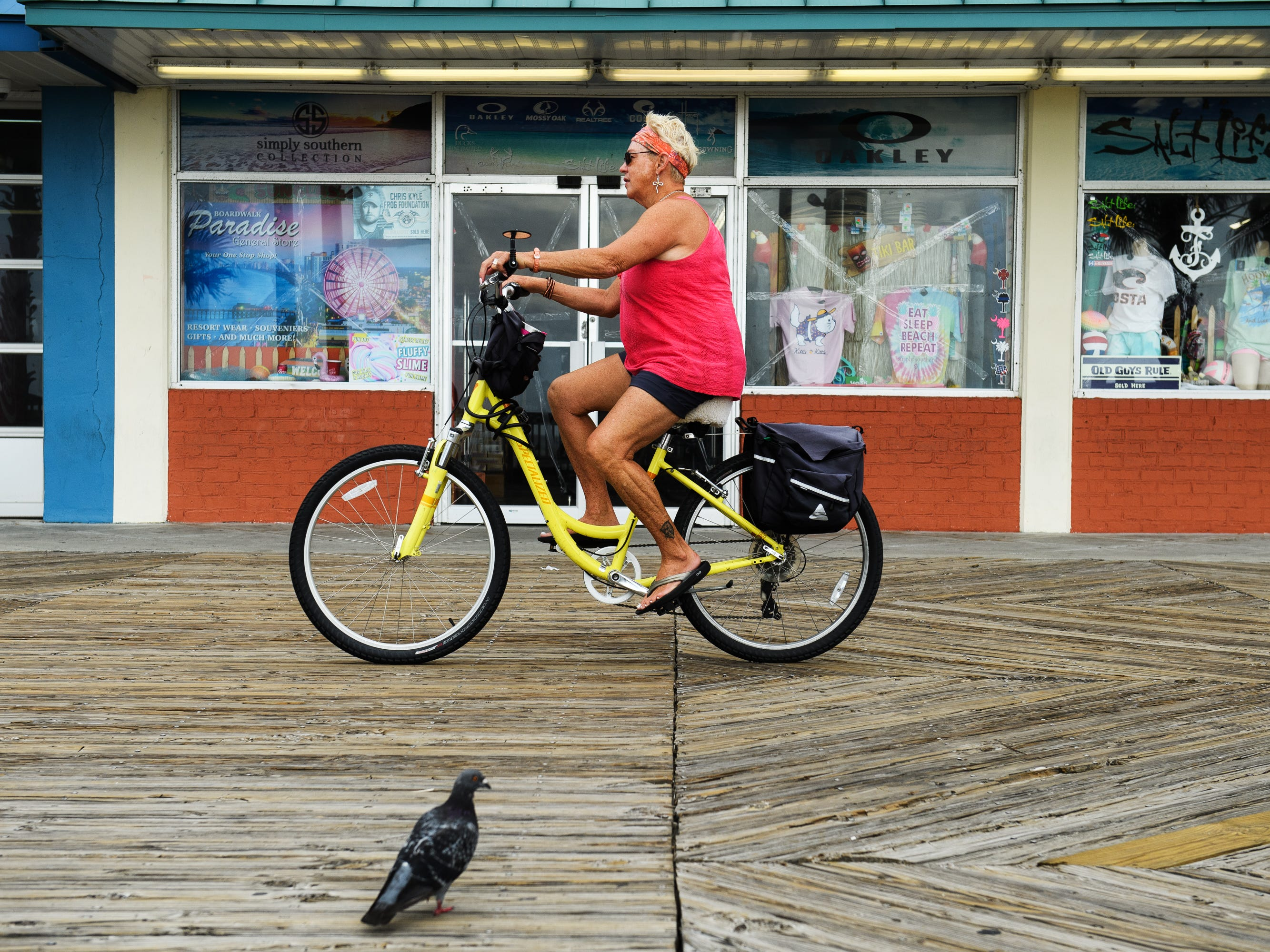 A woman rides her back at the Myrtle Beach Boardwalk and Promenade on Thursday, Sept. 13, 2018 hours before Hurricane Florence is expected to hit the area.