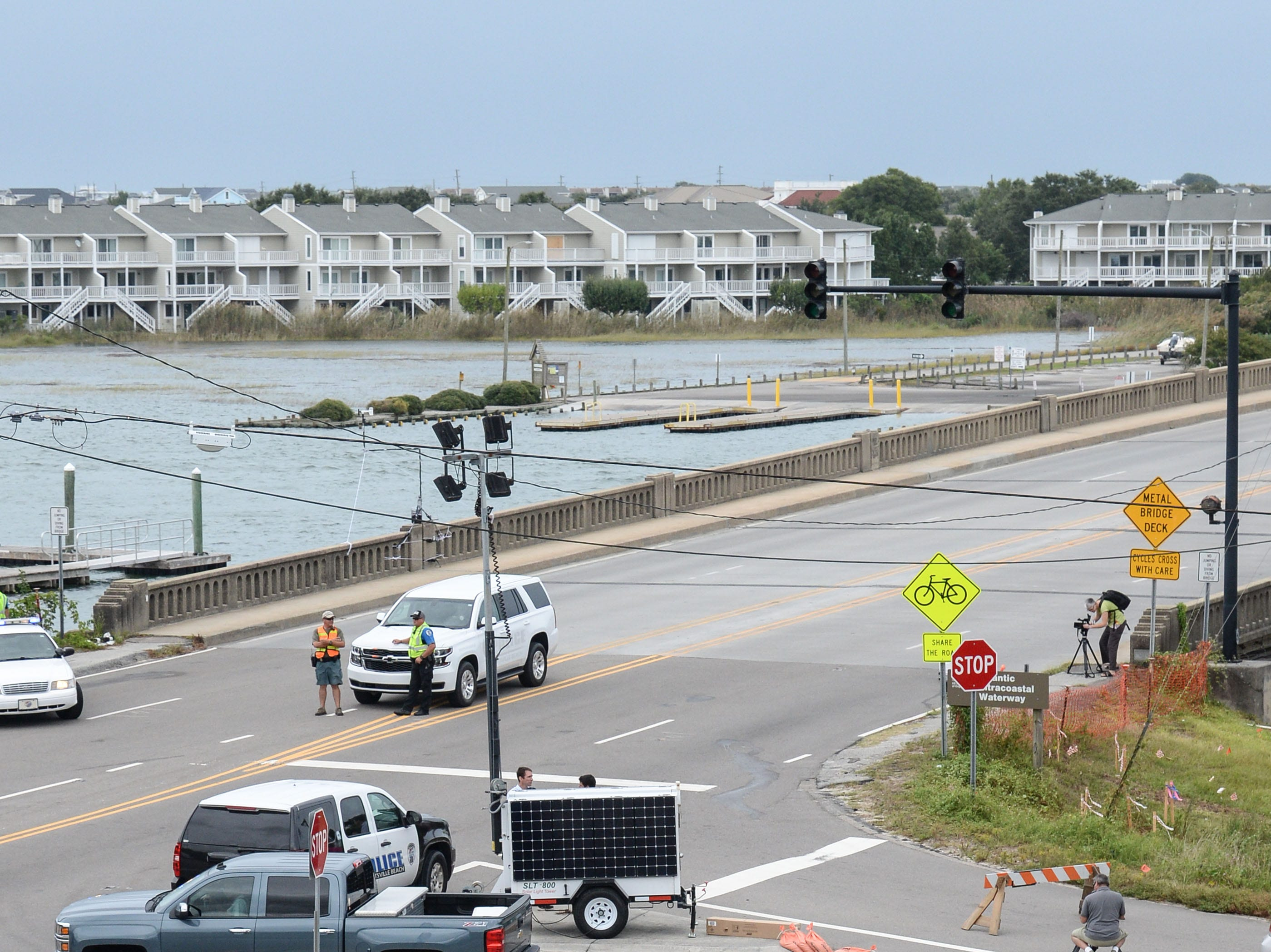 Two people walk their dog by a roadblock at a bridge to Wrightsville Beach and the Waterway Lodge in Wilmington, North Carolina on Thursday, September 13, 2018. Freed arrived Tuesday. (Ken Ruinard / Greenville News / Gannett USA Today Network / 2018 )