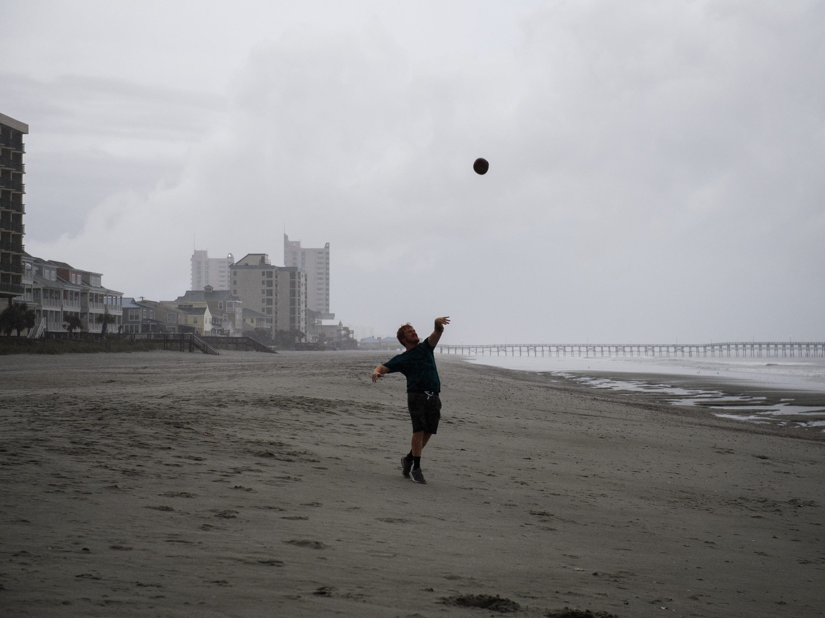 Noah Peele, 20, plays catch at Cherry Grove Beach in North Myrtle Beach as the first rain from a stray outer band of Hurricane Florence hits the area on Thursday, Sept. 13, 2018.