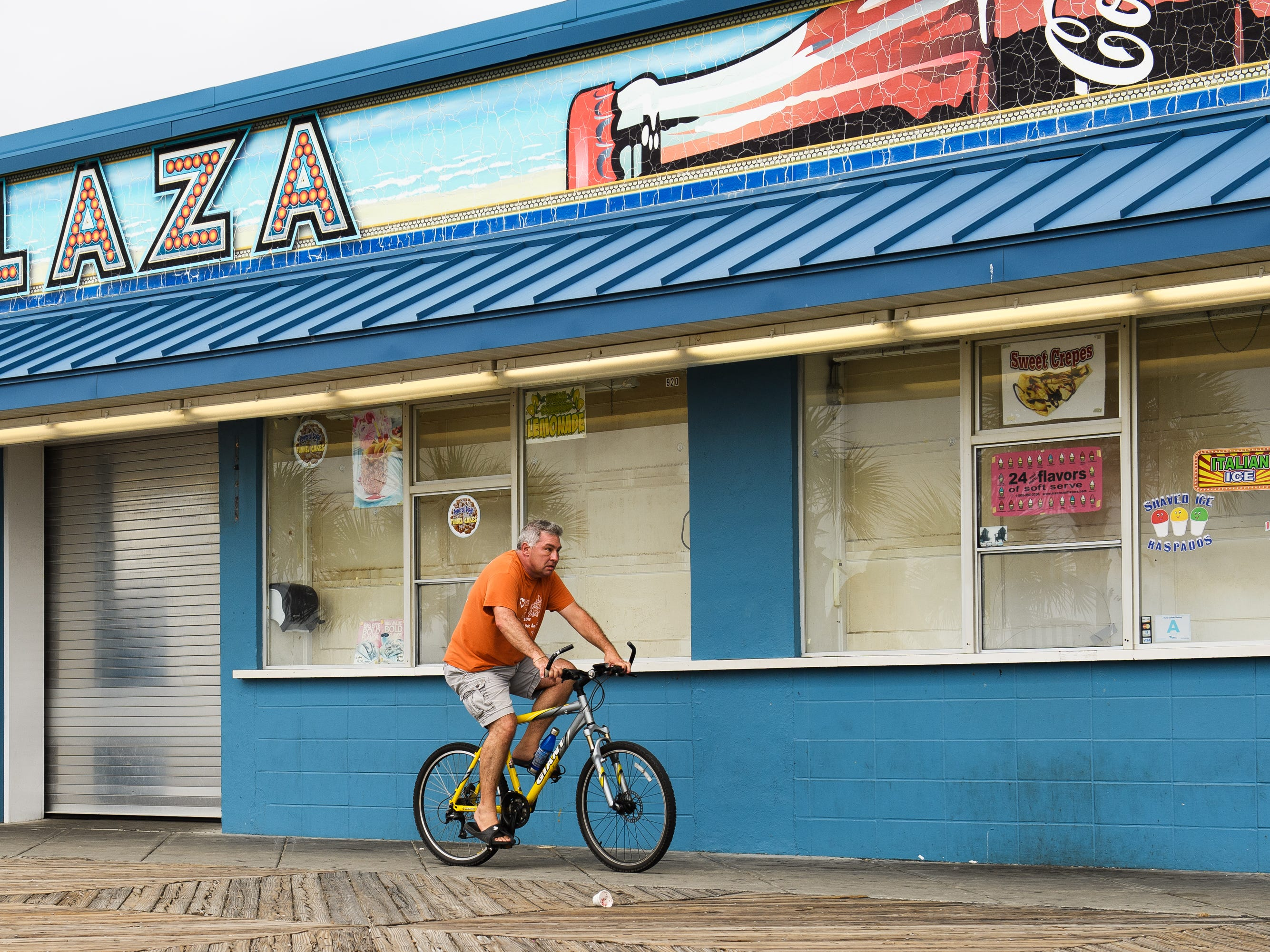 A man rides his bike at the Myrtle Beach Boardwalk and Promenade on Thursday, Sept. 13, 2018.