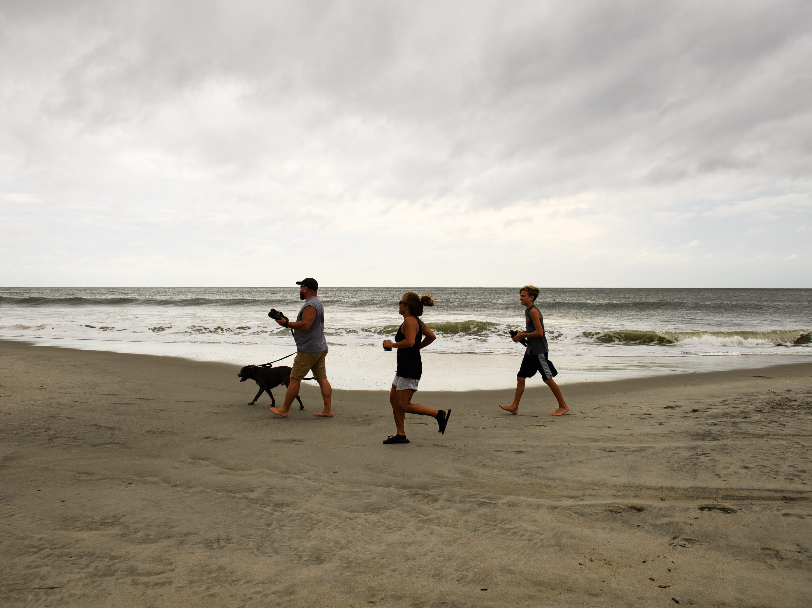 Jason, Melissa and Kaleb Hurley walk their dog Axel along the water at the Myrtle Beach Boardwalk and Promenade on Thursday, Sept. 13, 2018.
