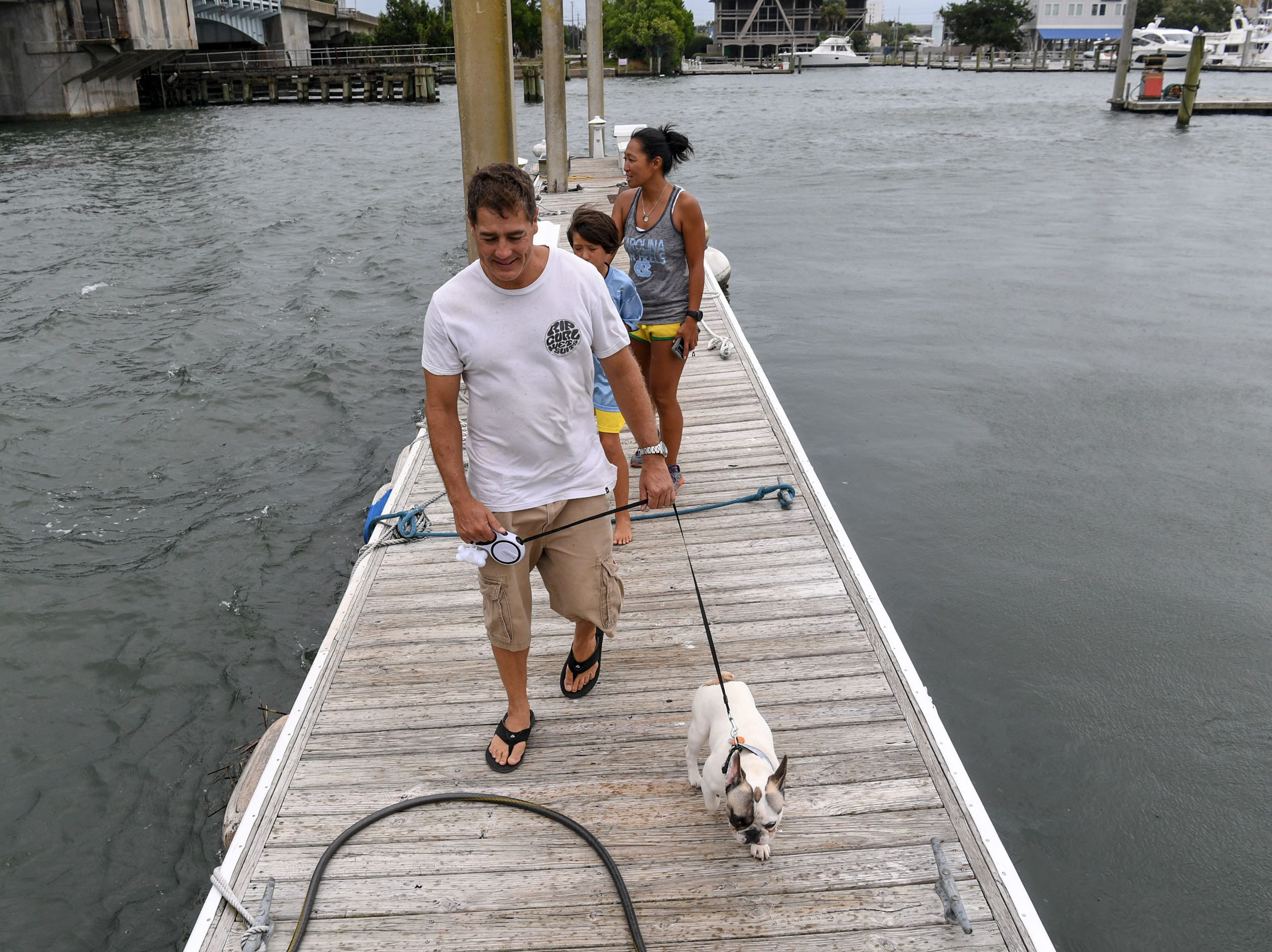 James Crowell walks Henry the dog while Kim Crowell and their son Gavin Crowell walk off a dock with gusts of wind at Wrightville Beach marina in Wilmington, North Carolina on Thursday, September 13, 2018. (Ken Ruinard / Greenville News / Gannett USA Today Network / 2018 )