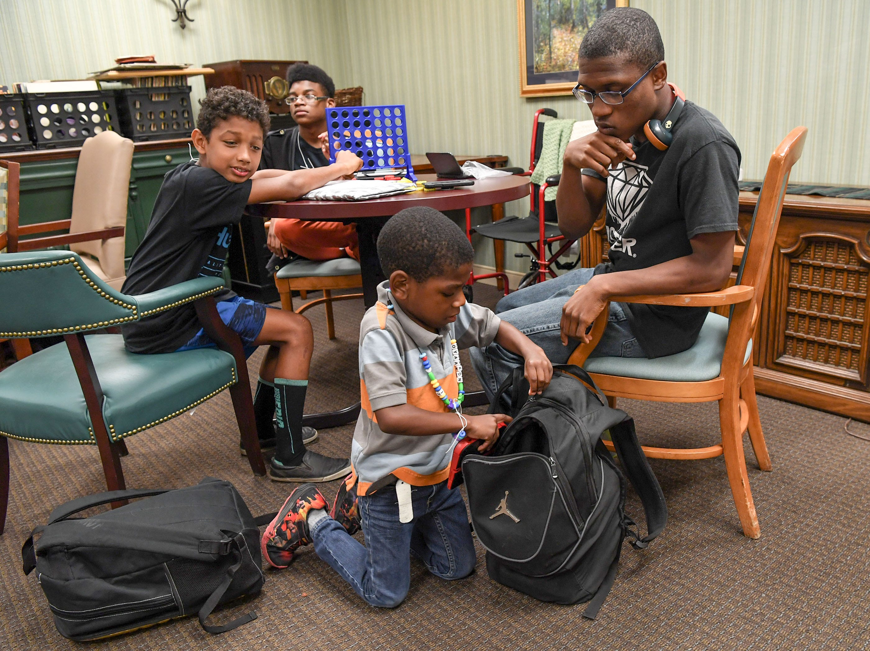 Jaeden Johnson, 8, below, gets into his brother Rae Walton, 19, near J.J. Lewis, 12, and William Royal, 14, at the Davis Community nursing home and assisted living facility in Wilmington, North Carolina on Thursday, September 13, 2018. The boys are with their family members who work at the facility and were allowed to join them at a safe place to stay during Hurricane Florence. (Ken Ruinard / Greenville News / Gannett USA Today Network / 2018 )