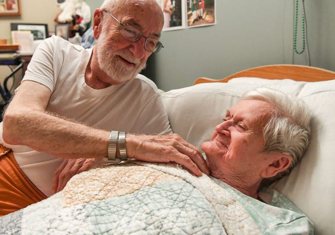 """Bob Derbyshire, left, lays next to his wife of 70 years, Joan Derbyshire, singing 'Itsy bitsy spider' at the Davis Community nursing home and assisted living facility in Wilmington, North Carolina on Thursday, September 13, 2018. """"She likes that song,"""" Bob explained. (Ken Ruinard / Greenville News / Gannett USA Today Network / 2018 )"""