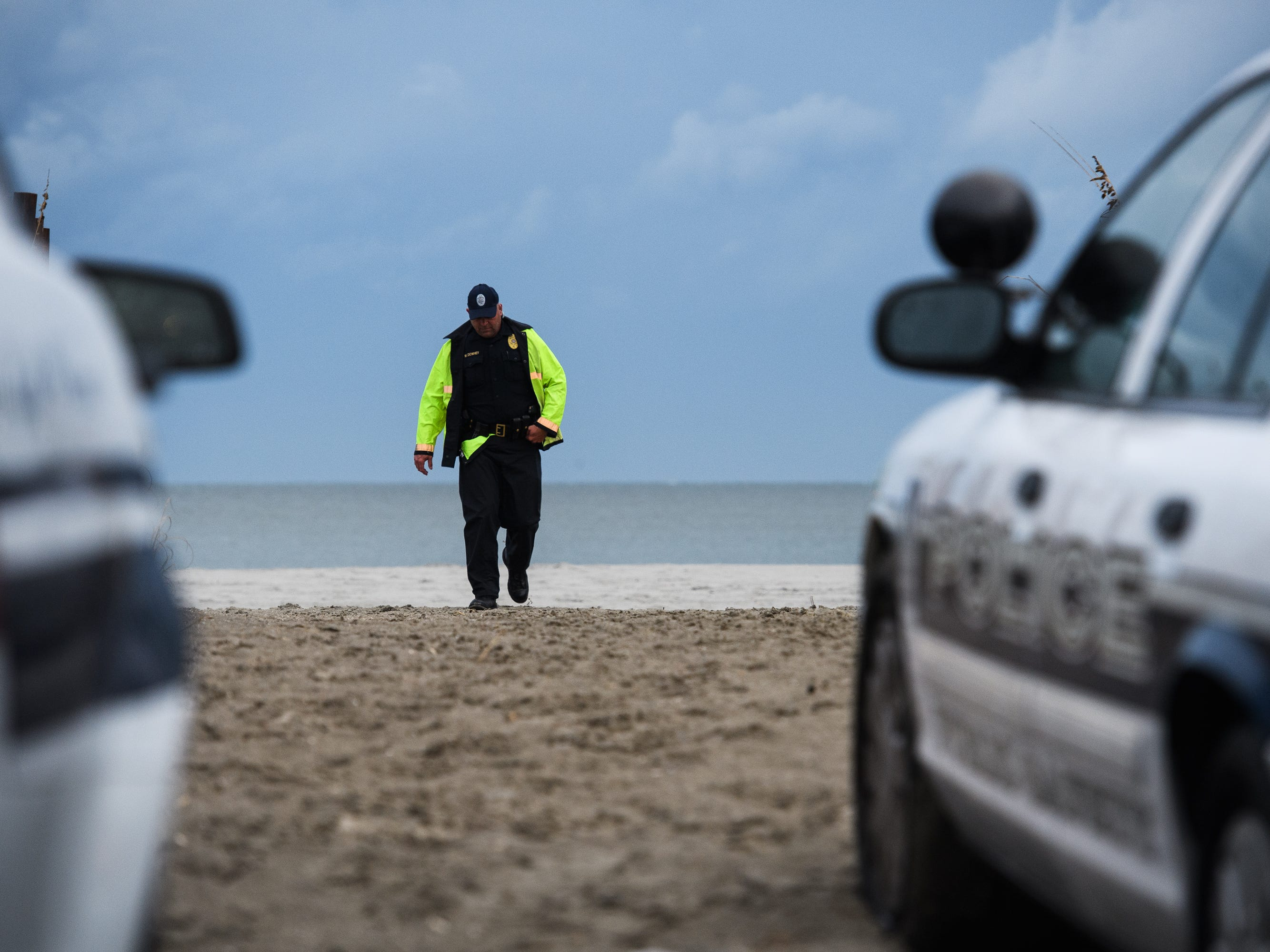 A North Myrtle Beach public safety officer walks back to his vehicle after informing beachgoers of a 7 p.m. curfew due to the arrival of Hurricane Florence on Thursday, Sept. 13, 2018.