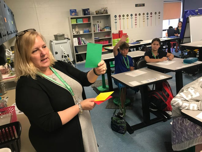 Heidi Bishop, principal of Lakes and Bridges Charter School, shows colored cards students use to let their teacher know if they want to answer a question in class.