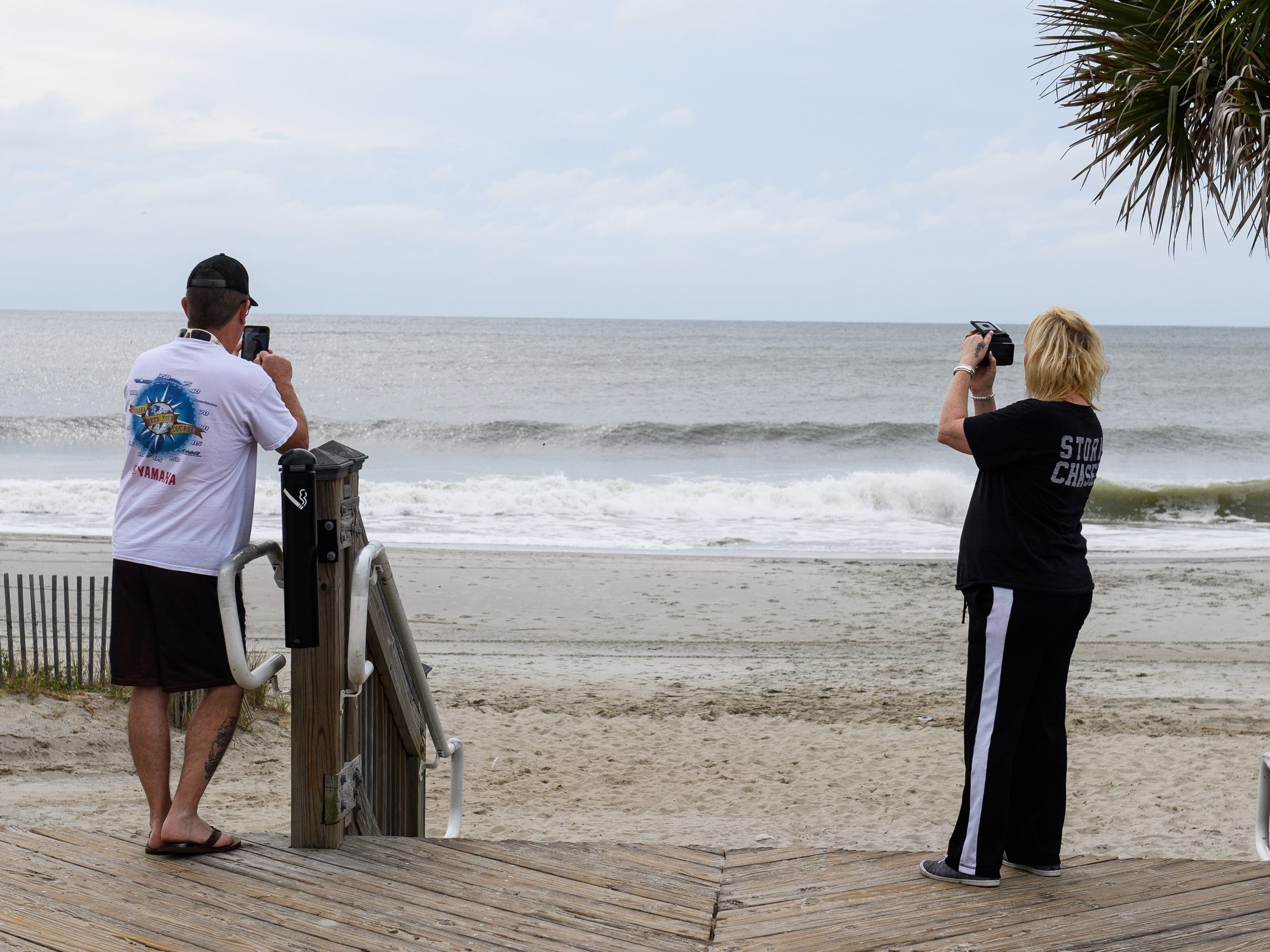 Stormy Walls and her husband Rick take photographs of the beach at the Myrtle Beach Boardwalk and Promenade on Thursday, Sept. 13, 2018.
