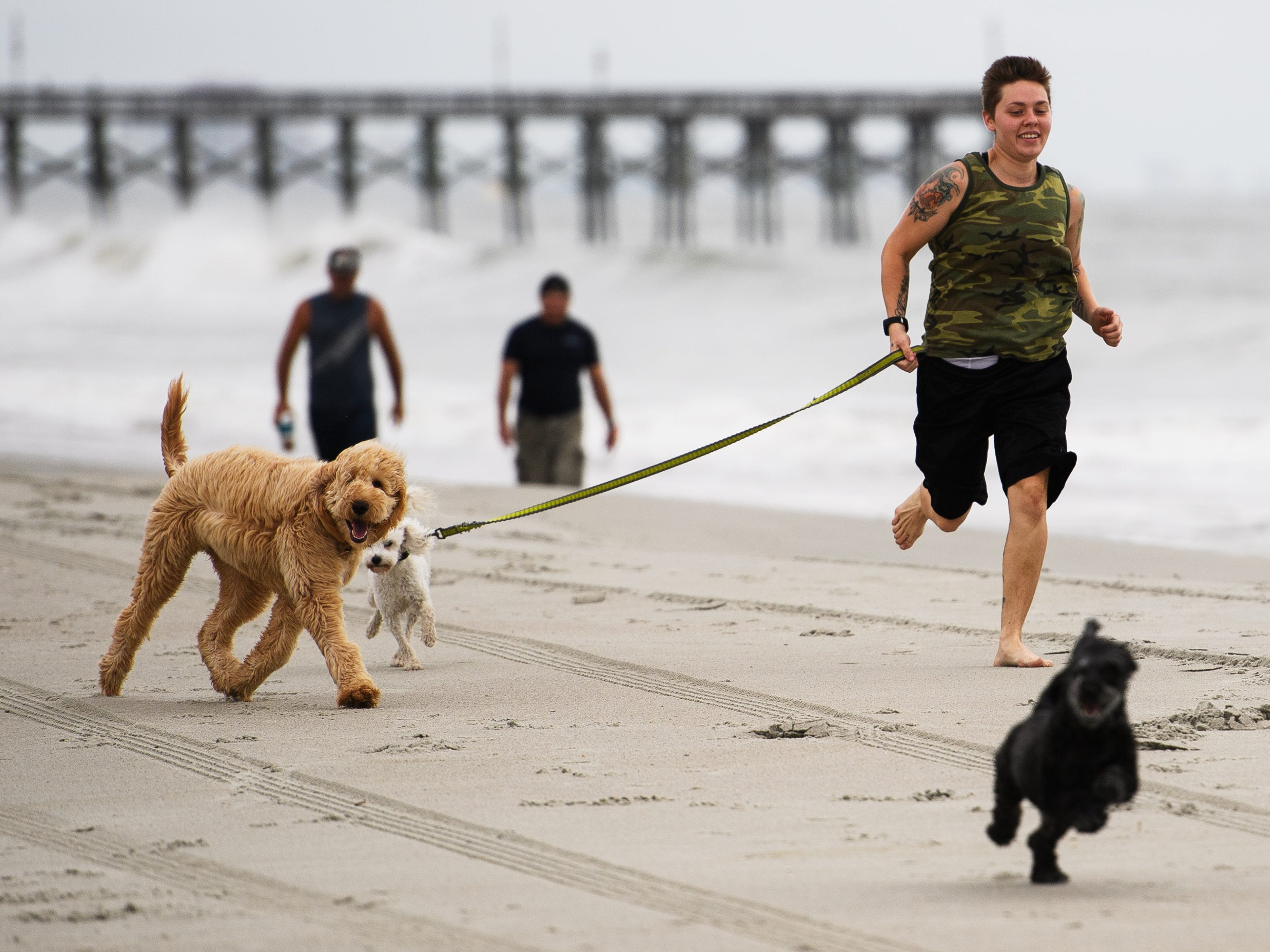Tiffany Marshall runs down the beach with her dogs Carter, Butters and Courage near the Myrtle Beach Boardwalk and Promenade on Thursday, Sept. 13, 2018.