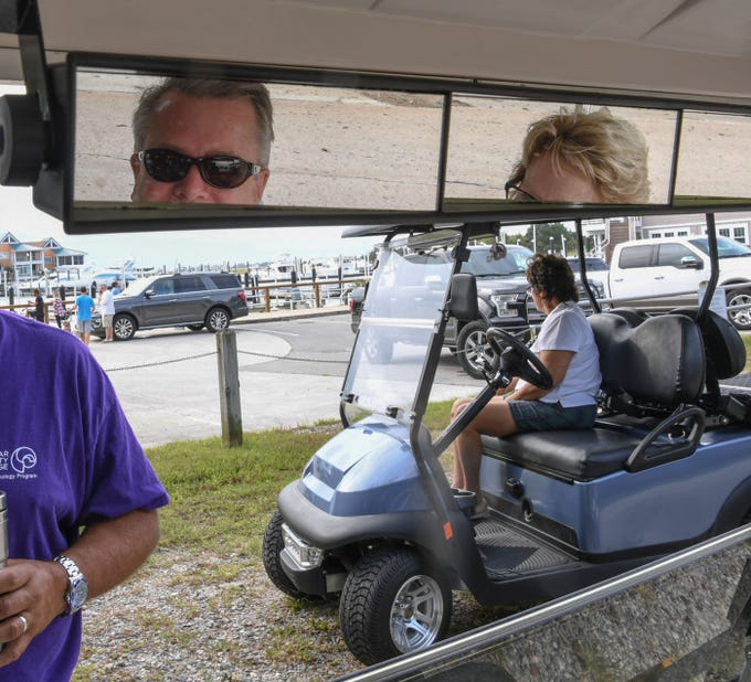 Steve Wells, left, and his wife Bonnie Wells, right, of Wilmington, North Carolina watch Jim Cantore, middle, of The Weather Channel at Crocker's Landing harbor in Wilmington, N.C., before Hurricane Florence hit on Thursday, September 13, 2018. (Ken Ruinard / Greenville News / Gannett USA Today Network / 2018 )
