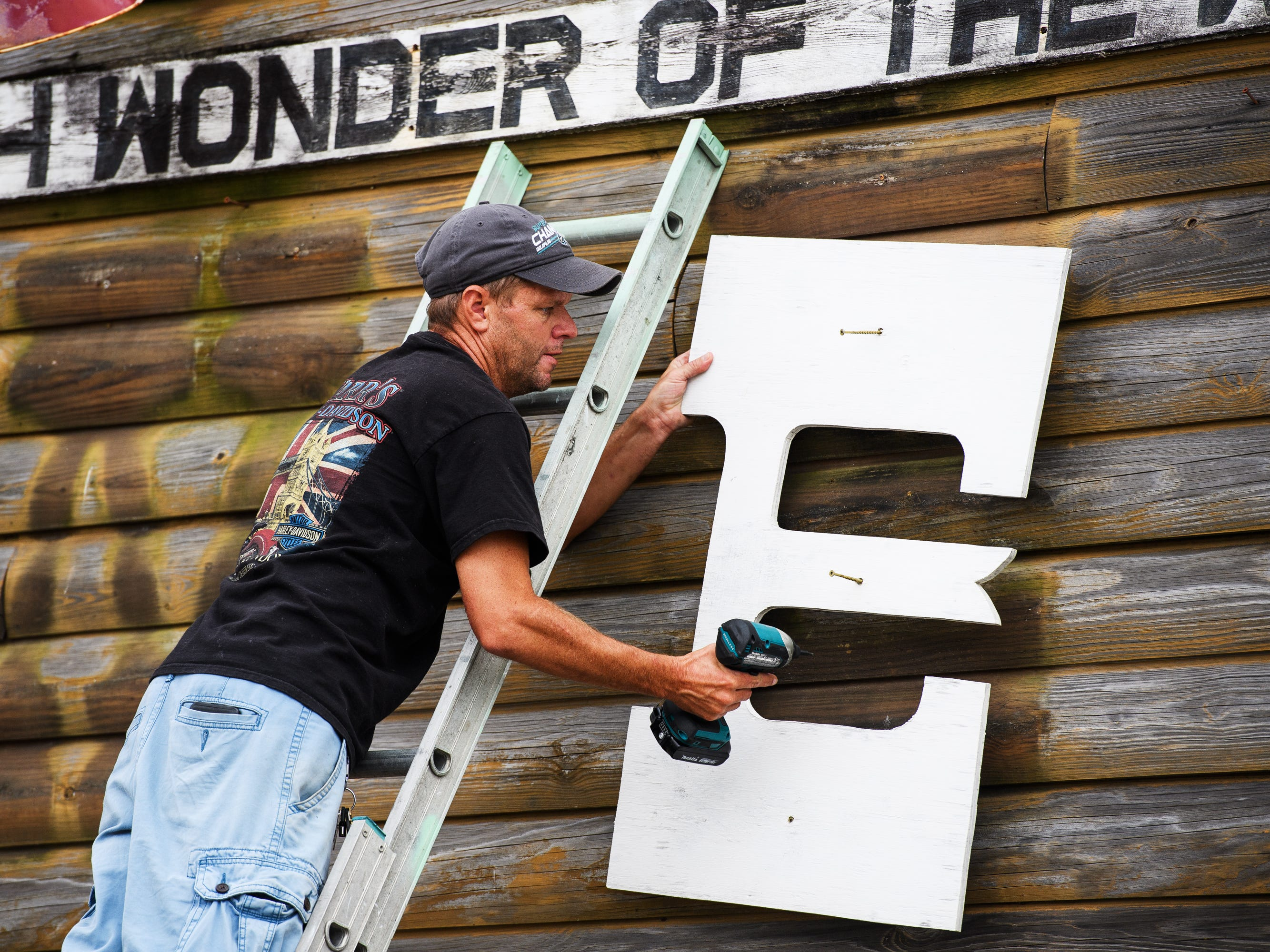 Pete Bissell takes the letters off the sign at the Bowery at the Myrtle Beach Boardwalk and Promenade on Thursday, Sept. 13, 2018.