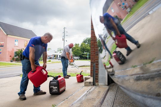 Swan Quarter N.C fire chief Jefferey Stotesberry and his son J.T Stotesberry refuel generators and chainsaws at the fire department as they prepare for Hurricane Florence Sept. 13, 2018.