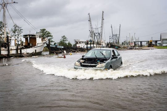 A motorist drives through a flooded area in the Swan Quarter harbor in Swan Quarter, N.C ., as Hurricane Florence makes landfall Sept. 13, 2018.