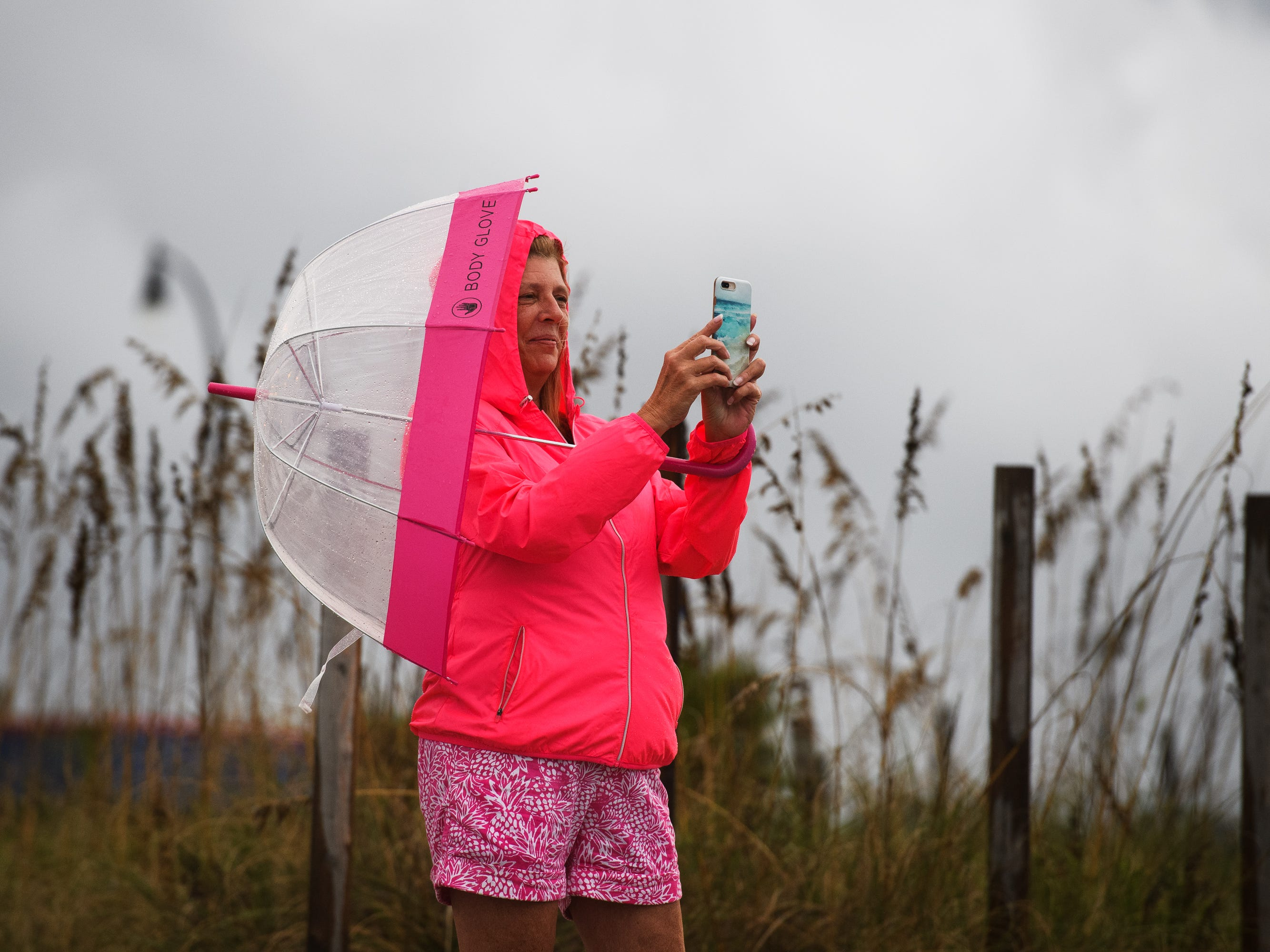 Karen Glass takes photos of the the shore at Cherry Grove Beach after the first rain from a stray outer band of Hurricane Florence hit the area on Thursday, Sept. 13, 2018.