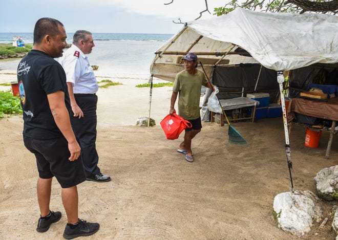 Fisherman Rick Rivera, right, thanks Capt. Tom Stambaugh, Guam Corps officer and Micronesia Coordinator for The Salvation Army, center, for handout of non-perishable foods and bottles of water during the Corps' visiting to Rivera's campsite at First Beach in Talofofo on Thursday, Sept. 13, 2018. Rivera, 55, says he makes a living by selling fish that he catches off the reefline during the past year. Rivera said he sought refuge at a relative's home during the passsage of Typhoon Mangkhut but upon his return, he found minimal damage sustained to his improvised beachside dwelling.