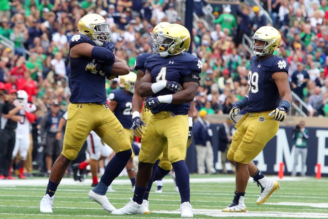 Notre Dame Fighting Irish defensive lineman Khalid Kareem (53), linebacker Te'von Coney (4) and defensive lineman Jerry Tillery (99) celebrate after a tackle against Ball State.