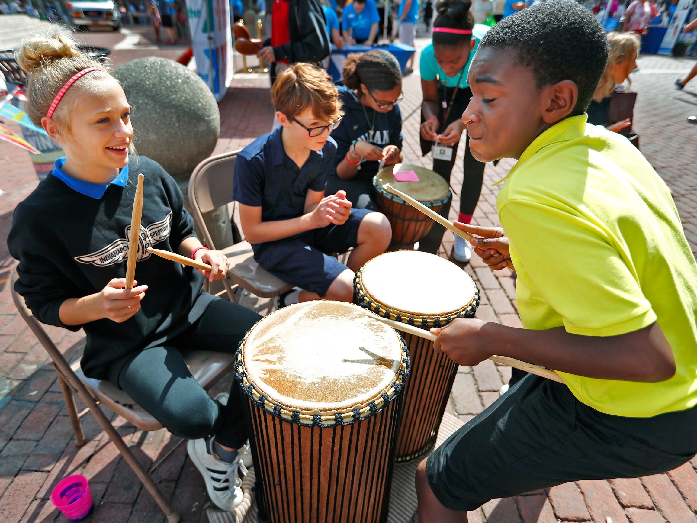 Center for Inquiry students Amy Bowling, from left, Sebastian Glass, Kiah Lehmkuhl, and Kendrick Carr play drums during the YMCA World Fest, on Monument Circle, Thursday, Sept. 13, 2018. YMCA of Greater Indianapolis hosts the free event that celebrates cultures including international food vendors, music, sports, and performers.