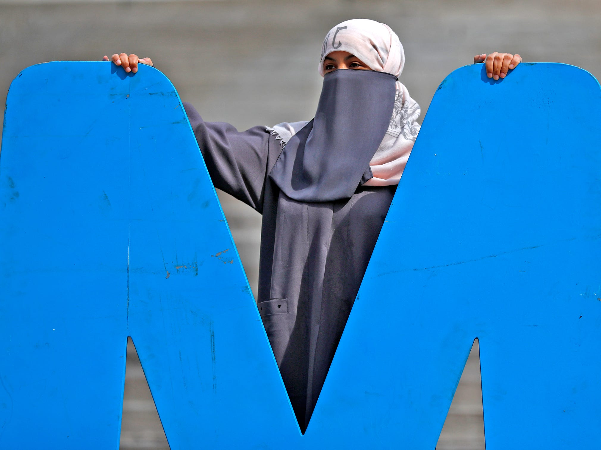 "Ibtisam Alruwaili poses with the ""M"" in the #YMCA sign during the YMCA World Fest, on Monument Circle, Thursday, Sept. 13, 2018. She joins other ESL Language Center students at the event. YMCA of Greater Indianapolis hosts the free event that celebrates cultures including international food vendors, music, sports, and performers."