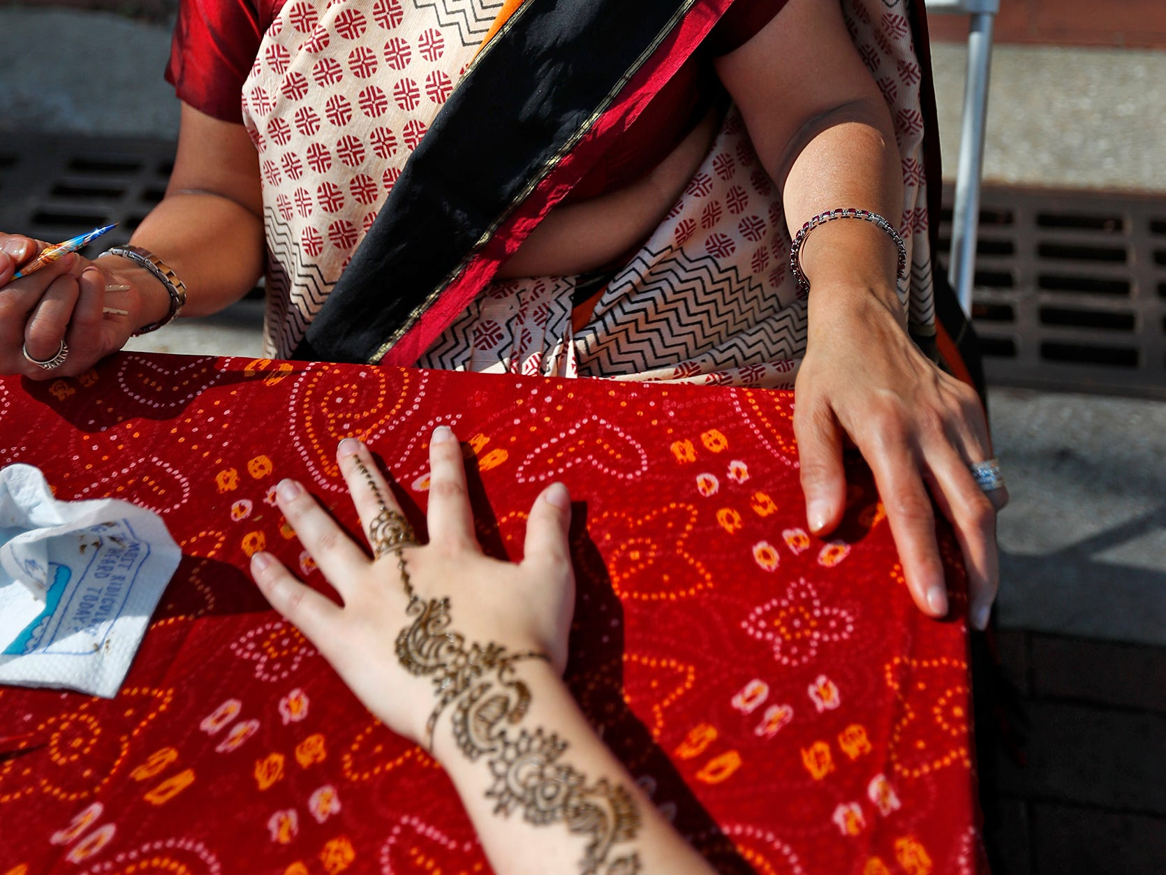 Parul Shah, left, smiles after finishing a henna tattoo on Libby Hancock during the YMCA World Fest, on Monument Circle, Thursday, Sept. 13, 2018. YMCA of Greater Indianapolis hosts the free event that celebrates cultures including international food vendors, music, sports, and performers.