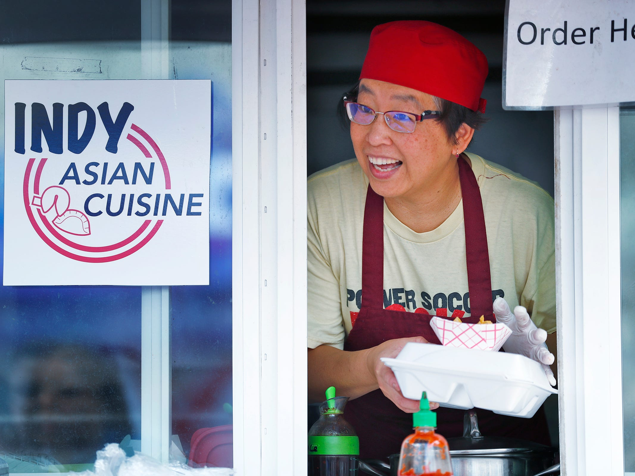 "Peiming ""Sonny"" Sun, with Rolling Asian Delight and Indy Asian Cuisine, gives a customer their food during the YMCA World Fest, on Monument Circle, Thursday, Sept. 13, 2018. YMCA of Greater Indianapolis hosts the free event that celebrates cultures including international food vendors, music, sports, and performers."