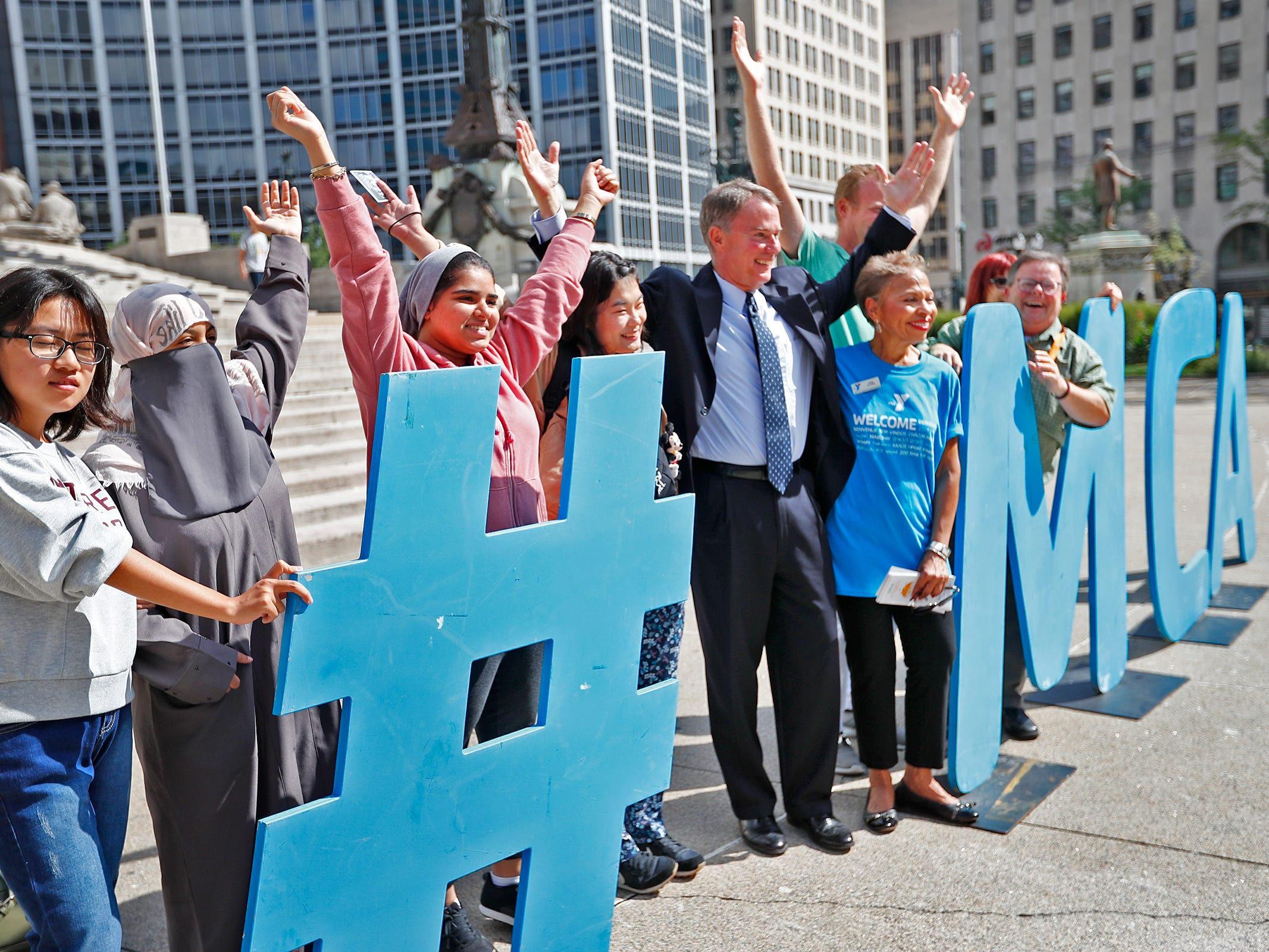 Mayor Joe Hogsett, center, poses with others for a photo with the giant #YMCA sign during the YMCA World Fest, on Monument Circle, Thursday, Sept. 13, 2018. YMCA of Greater Indianapolis hosts the free event that celebrates cultures including international food vendors, music, sports, and performers.